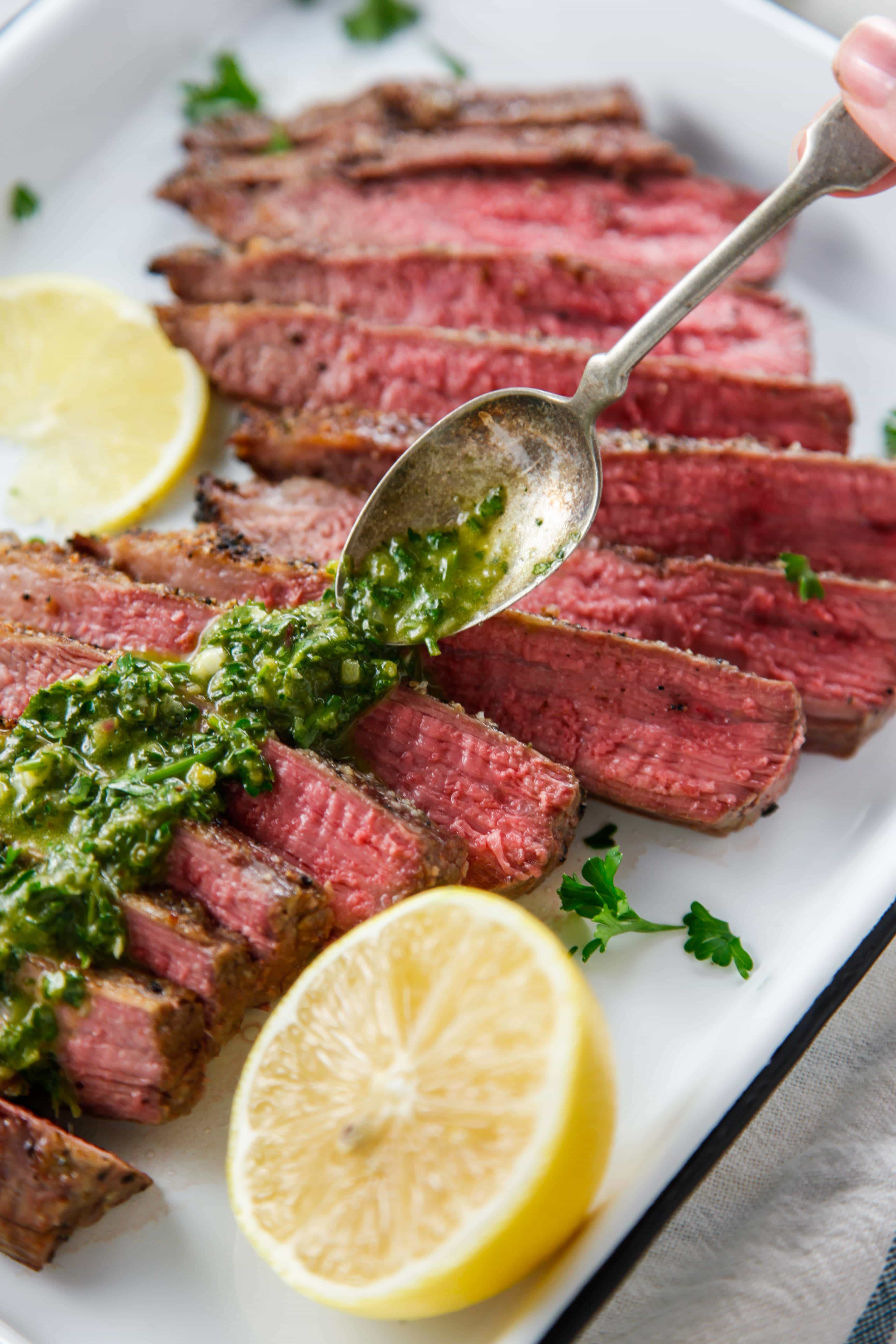 Broiled Flank Steak with Chimichurri being topped with sauce.