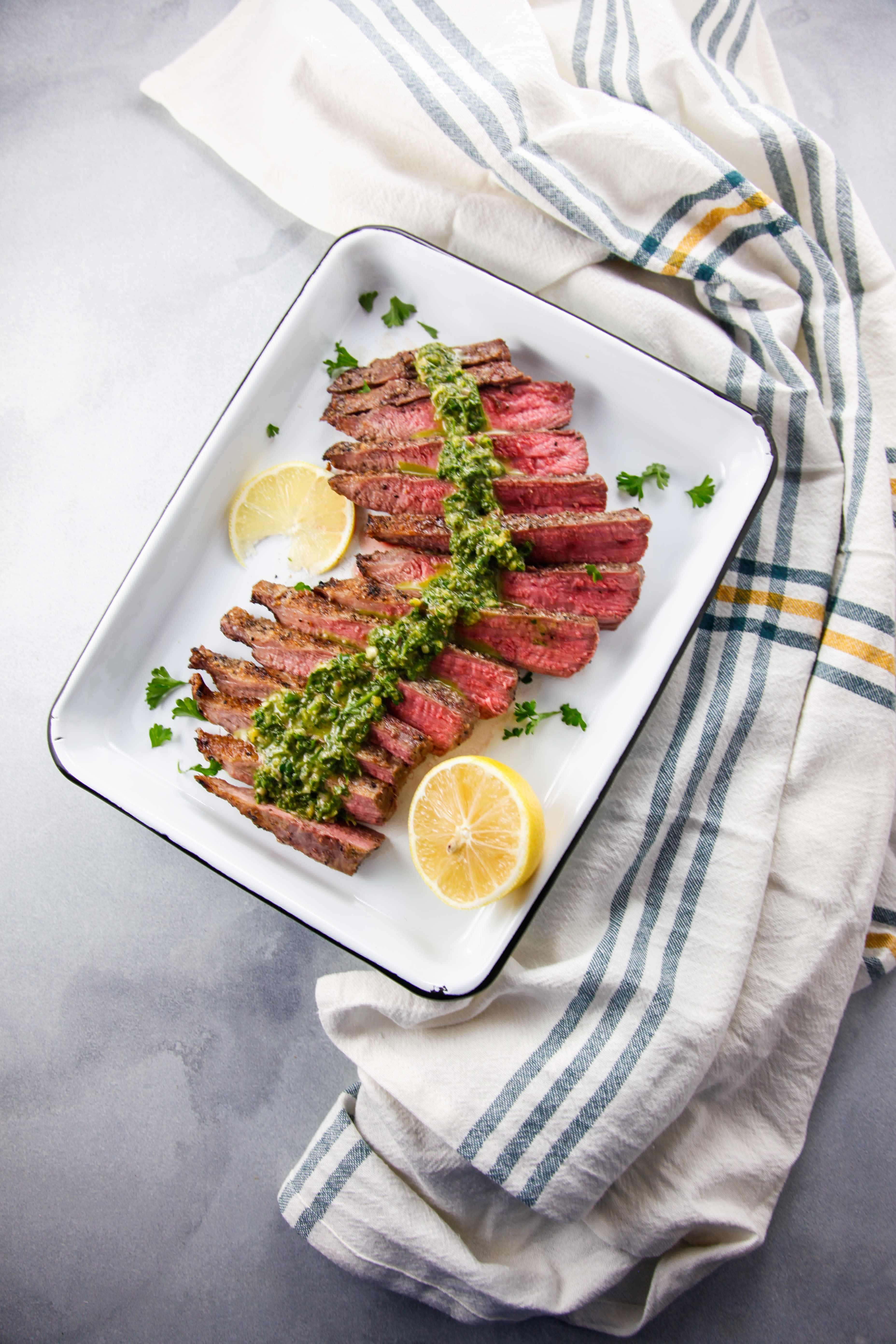 An overhead shot of Broiled Flank Steak with Chimichurri with a green striped napkin.