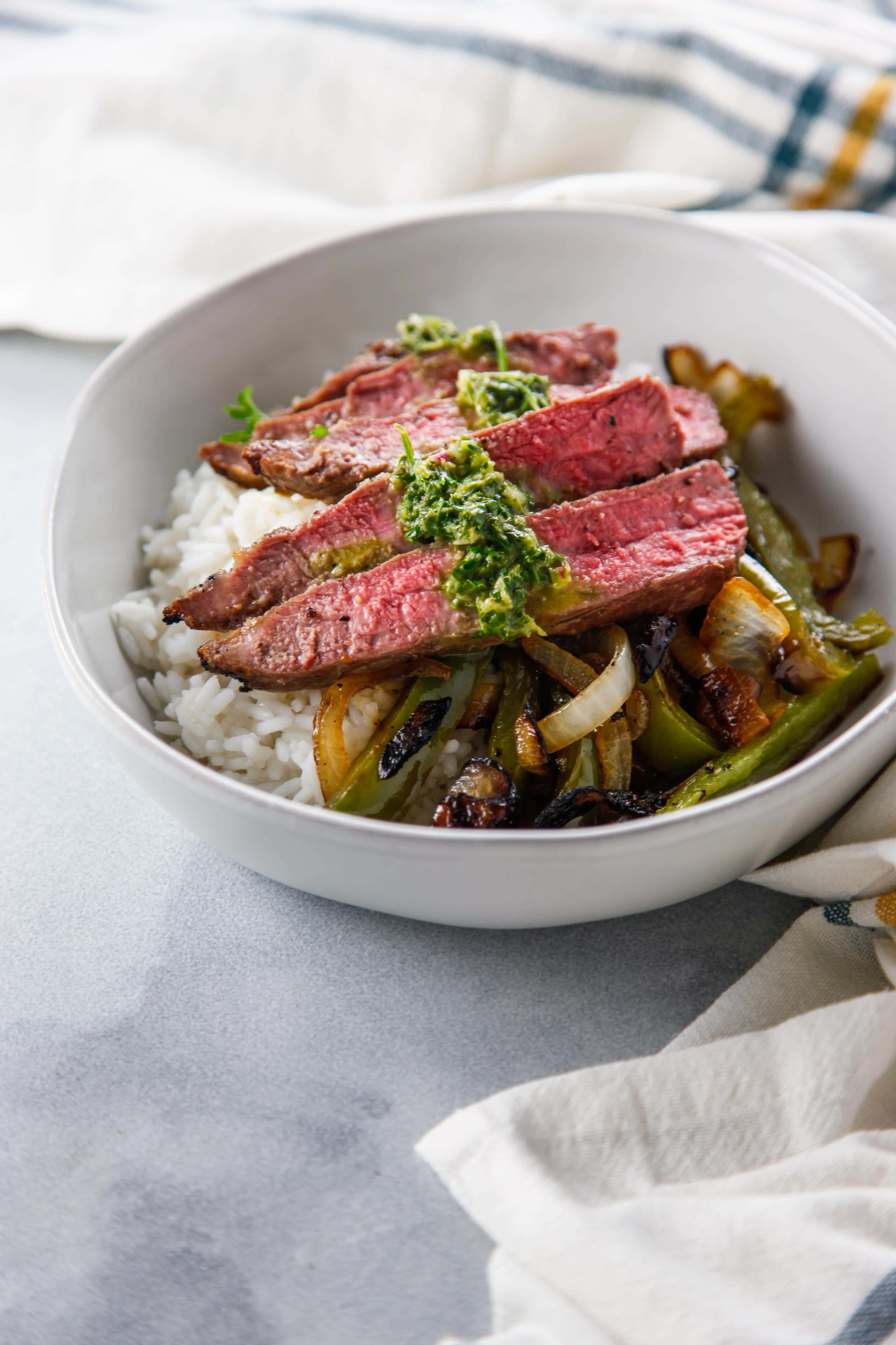 Broiled Flank Steak with Chimichurri in a white bowl with onions and peppers.