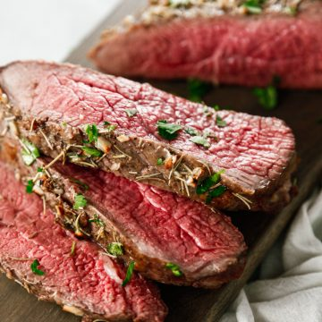 slices of Oven Baked Garlic Rosemary London Broil on a wooden cutting board.