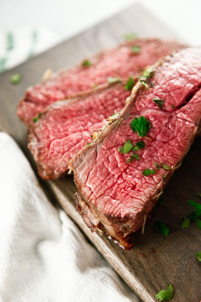 slices of Oven Baked Garlic Rosemary London Broil on a cutting board.