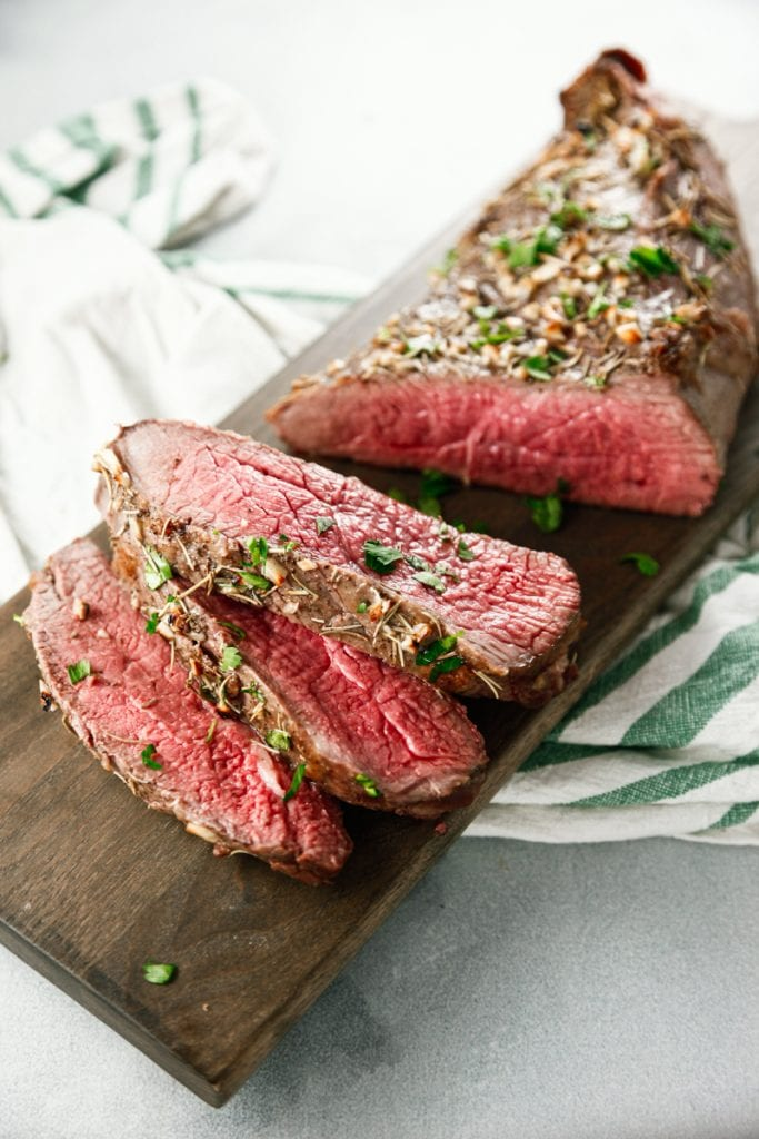 slices of Oven Baked Garlic Rosemary London Broil on a cutting board with a green and white kitchen towel.