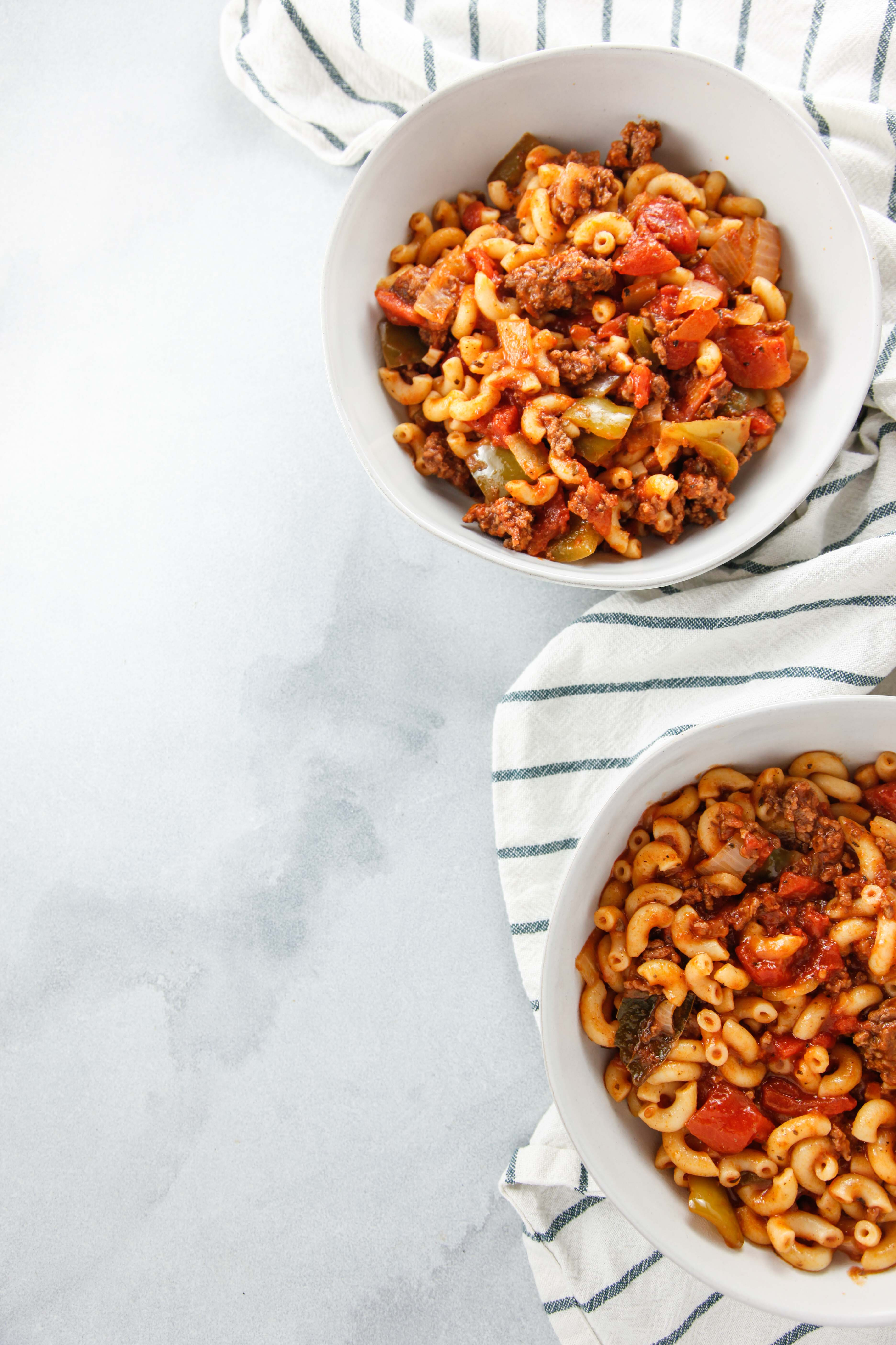 two white bowls full of Easy Saucy American Goulash.