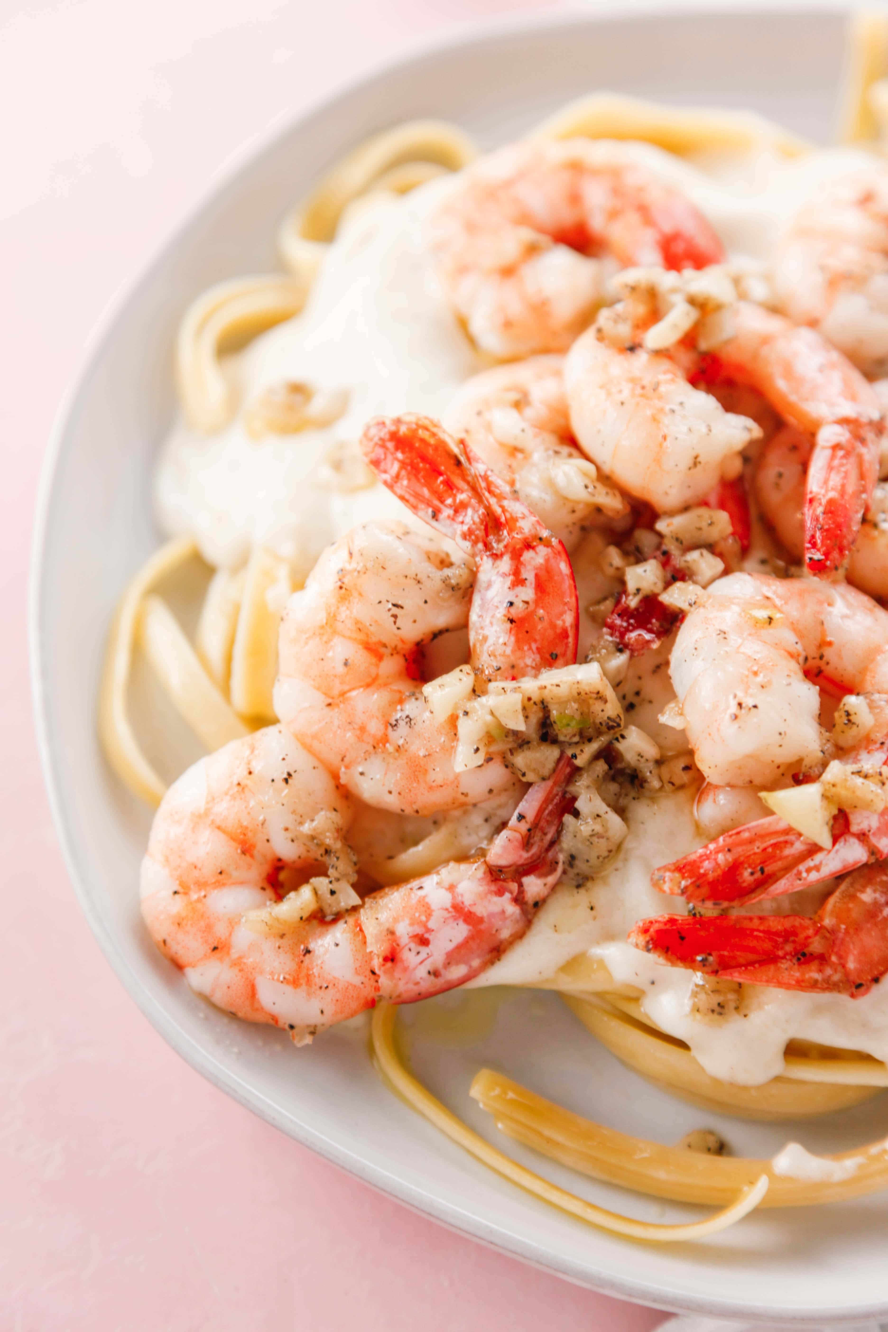 Garlicky Shrimp Fettuccine Alfredo on a white plate.