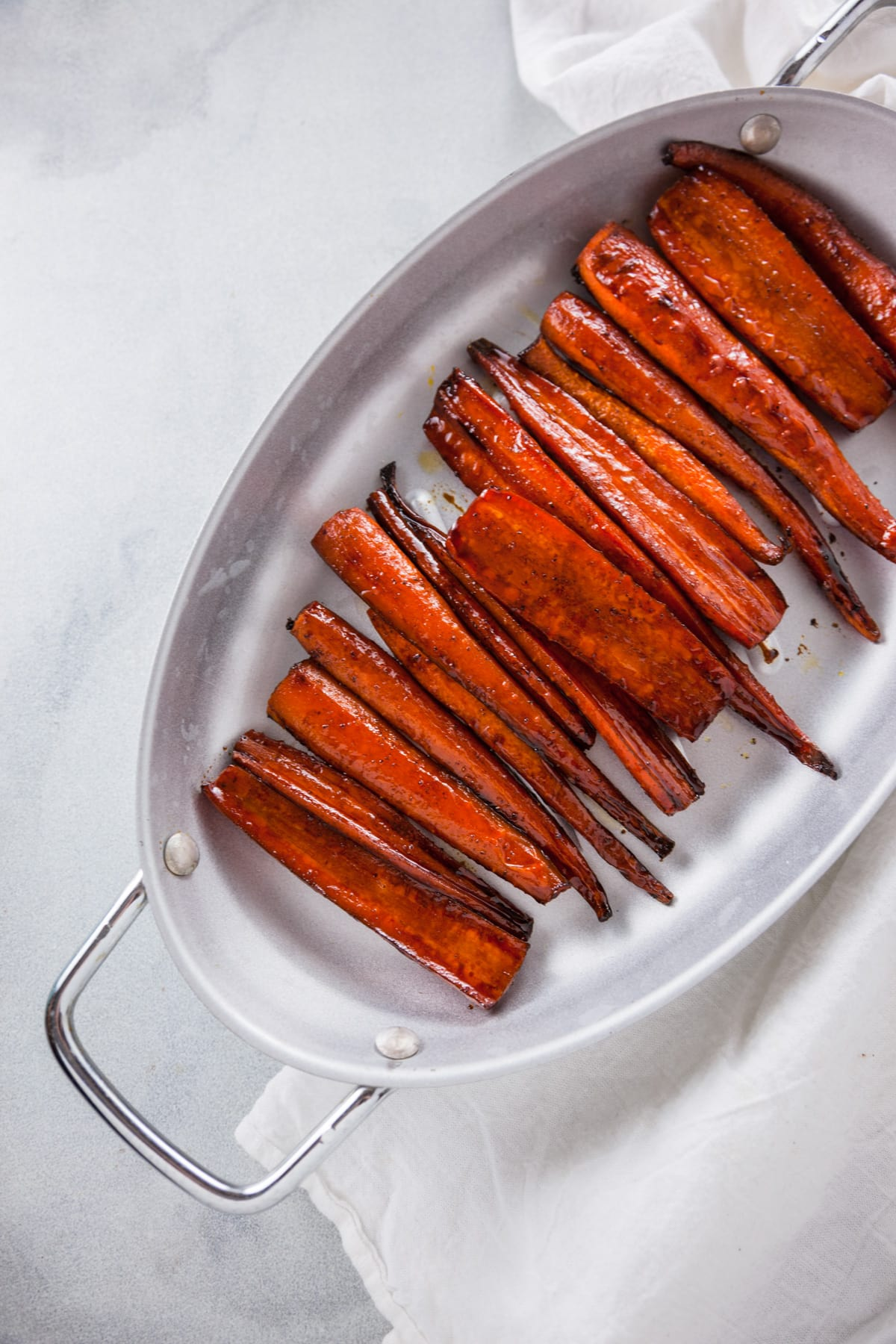 An overhead shot of Balsamic Glazed Roasted Carrots in a silver roasting pan.