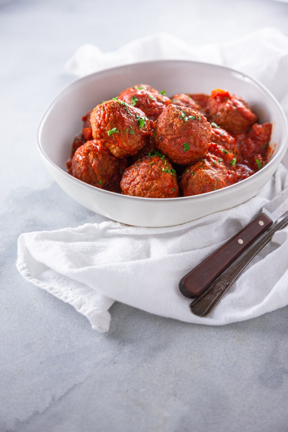 Italian Meatballs with Red Sauce in a white bowl with a napkin.
