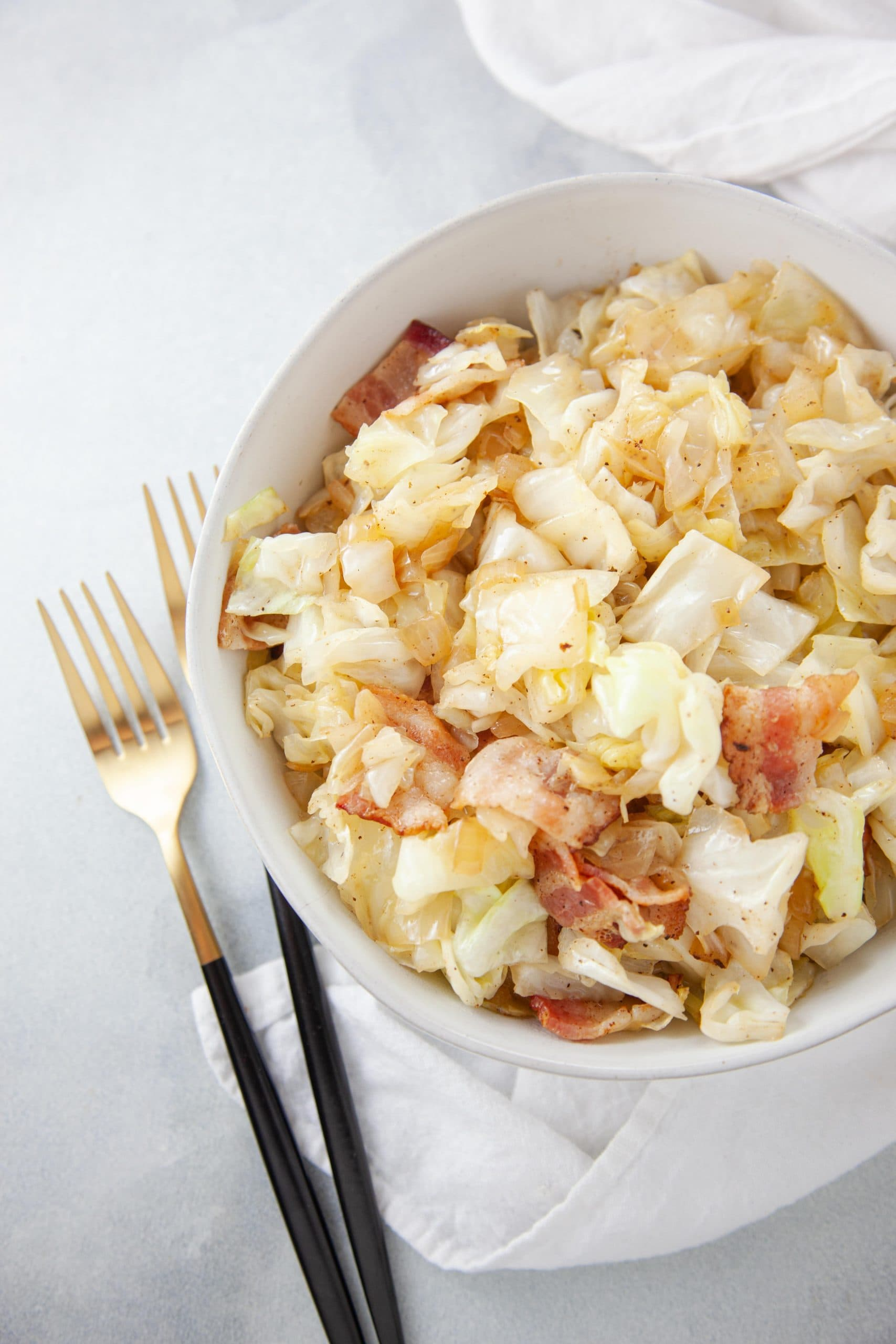 Southern Fried Cabbage and Bacon in a white bowl with black and gold silverware.