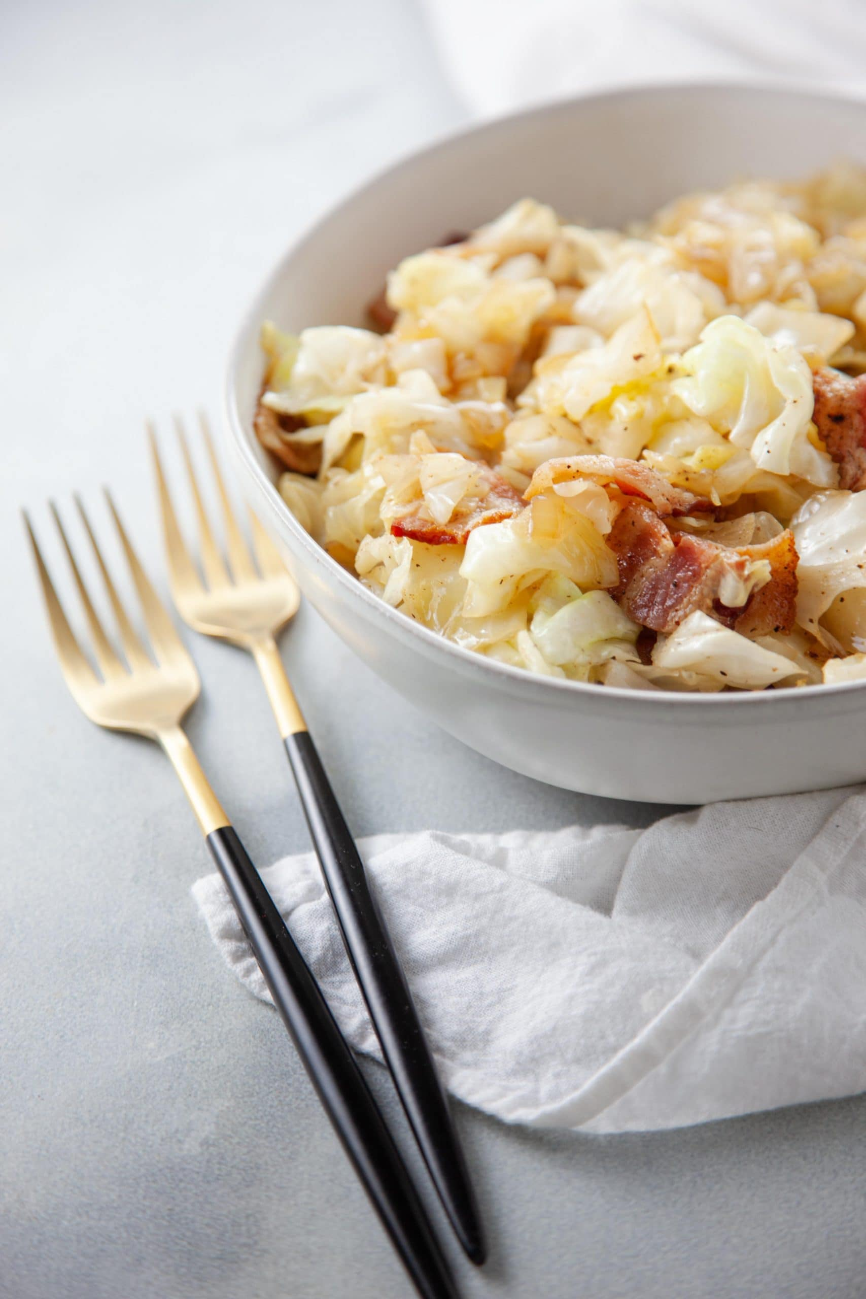 Southern Fried Cabbage and Bacon in a white dish with black and gold silverware.