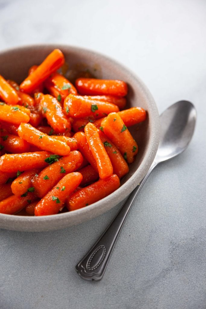 Apricot Garlic Glazed Carrots in a brown bowl.