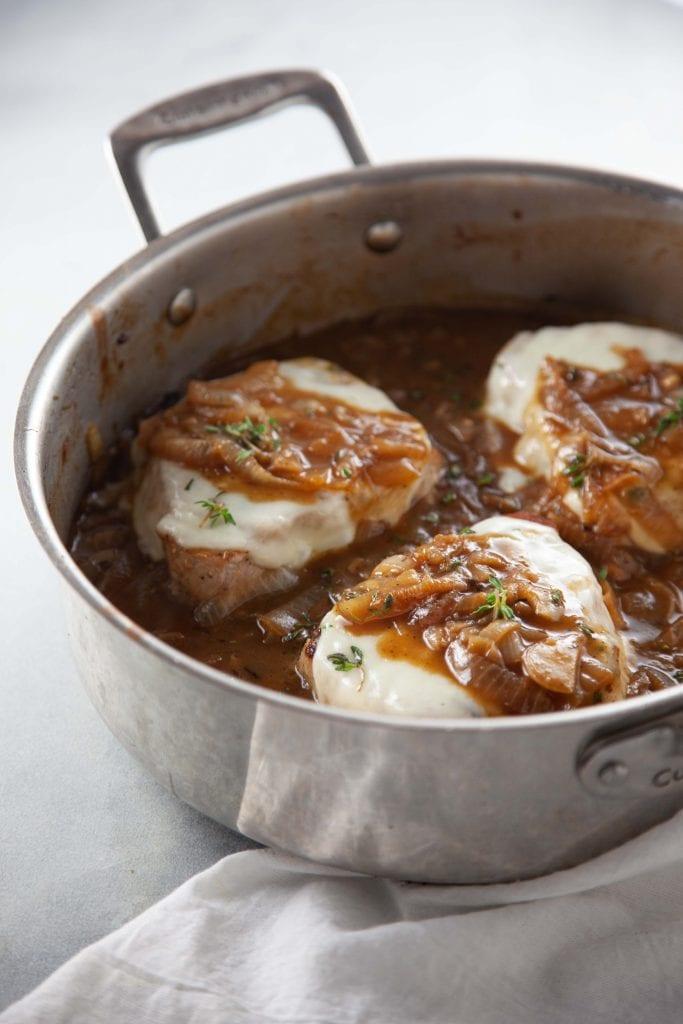 Three French Onion Pork Chops in a silver sauté pan.