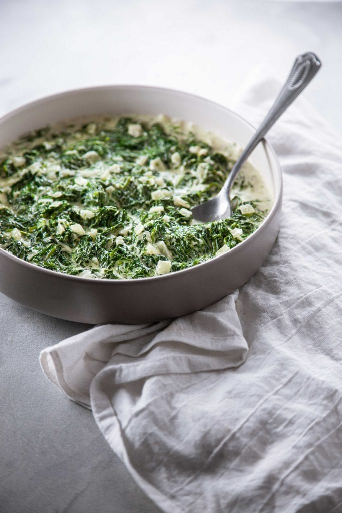 Easy Classic Creamed Spinach in a grey bowl and silver spoon.