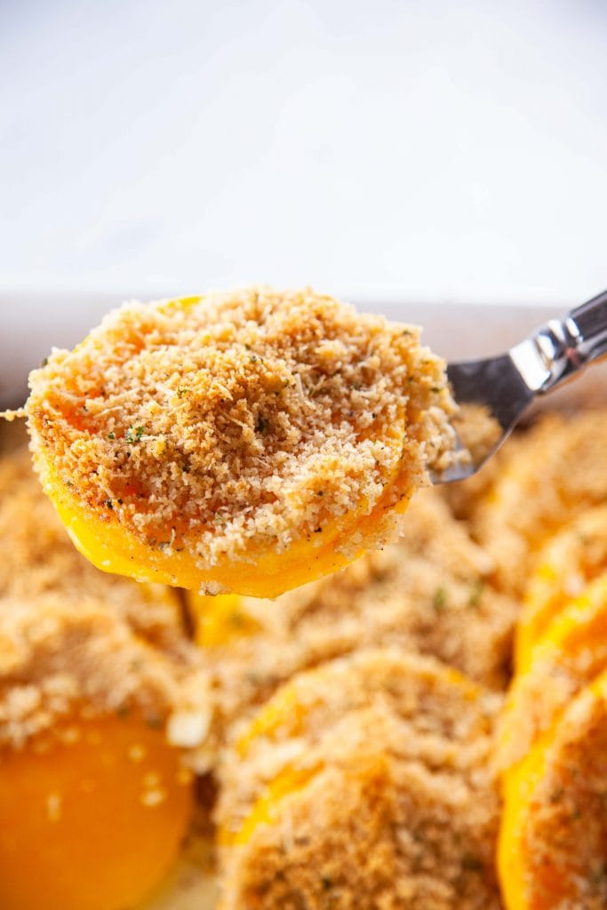 Butternut Squash Gratin lifted with a spatula out of a white baking dish.