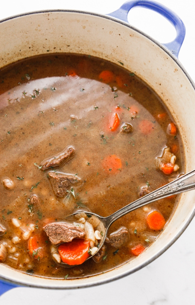 Beef and Barley Soup in a blue dutch oven with a silver spoon.