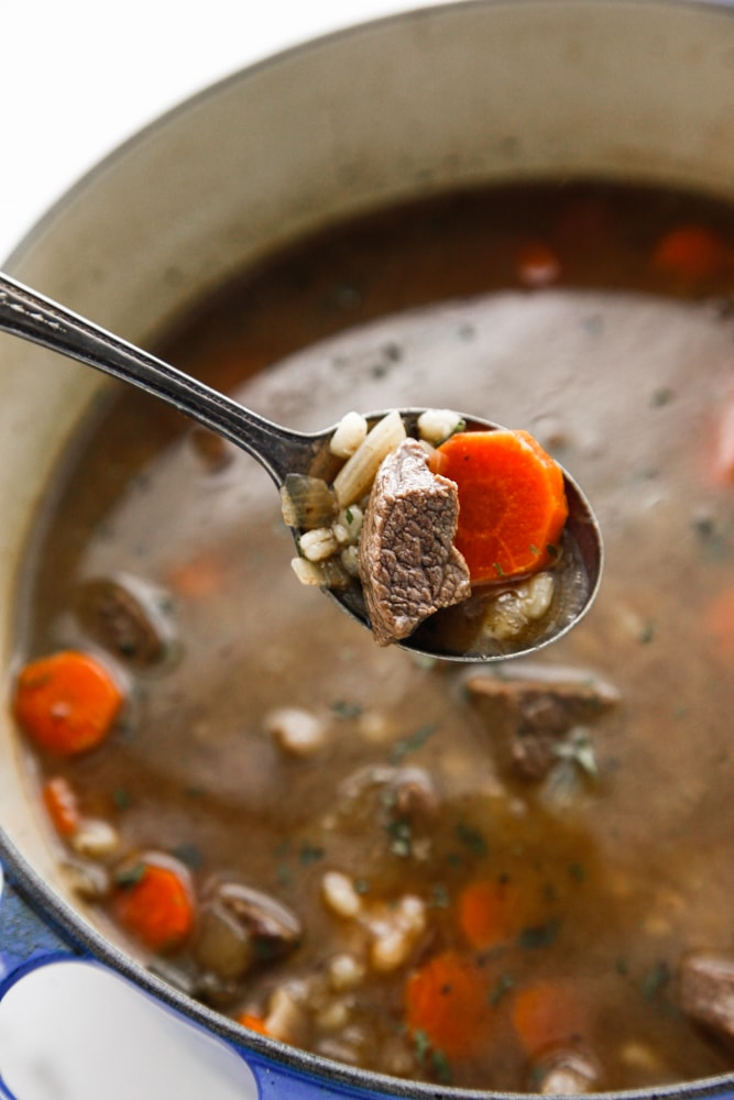 A spoonful of Beef and Barley Soup in a blue dutch oven.