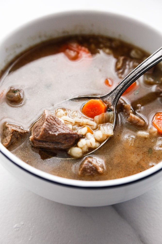 A spoonful of Beef and Barley Soup in a white bowl.