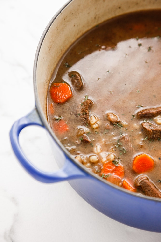 Beef and Barley Soup in a blue dutch oven.