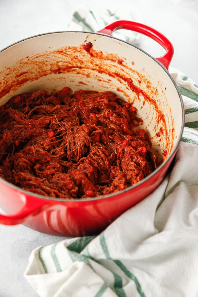 A red dutch oven full of shredded beef ragu.