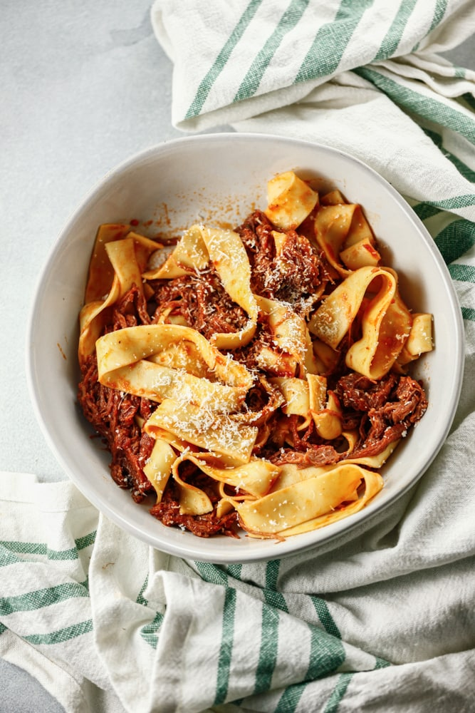 A white bowl full of Shredded Beef Ragu with Pappardelle with a green striped towel on the side.