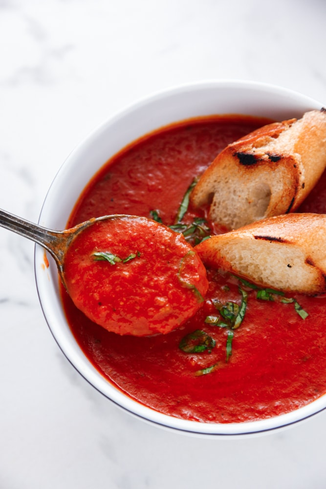 Roasted Red Pepper and Tomato Soup in a bowl with toasted bread.