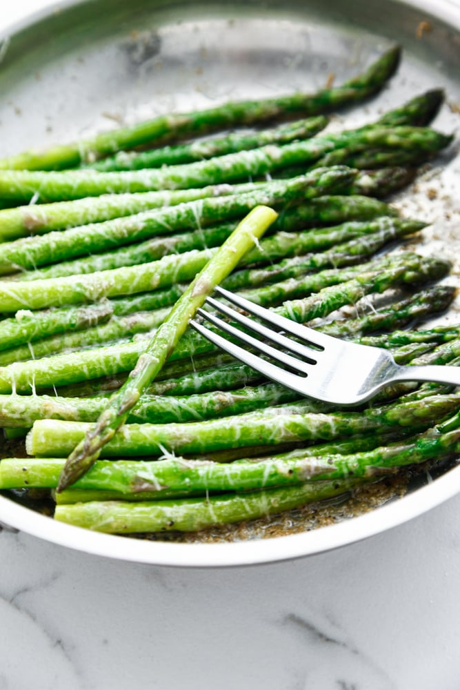 Brown Butter Parmesan Asparagus in a silver skillet with a fork.