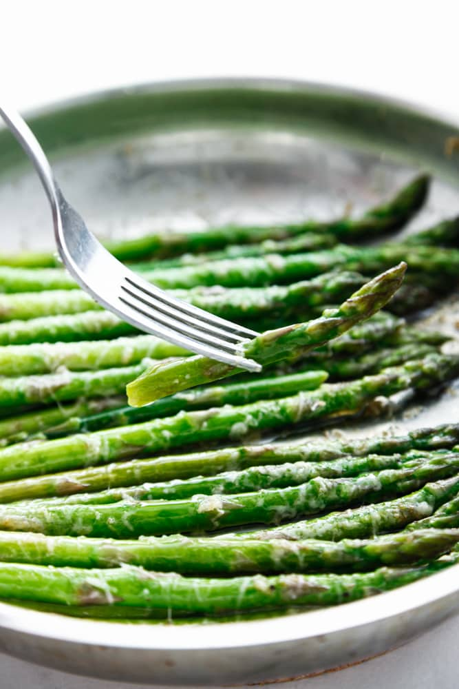 Brown Butter Parmesan Asparagus being lifted with a fork.