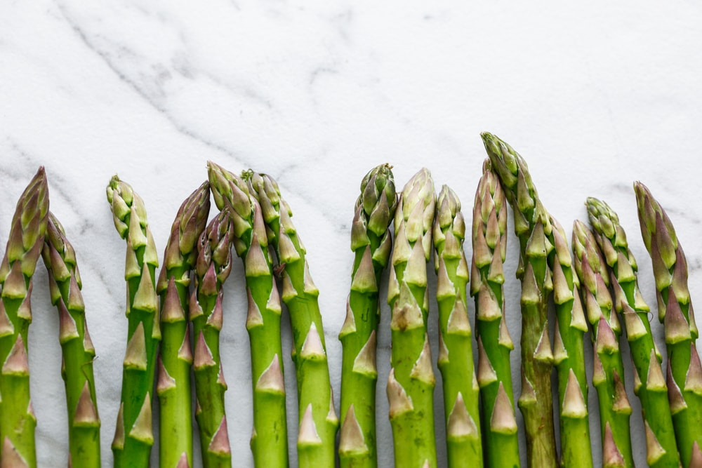 raw asparagus lined up in a row.