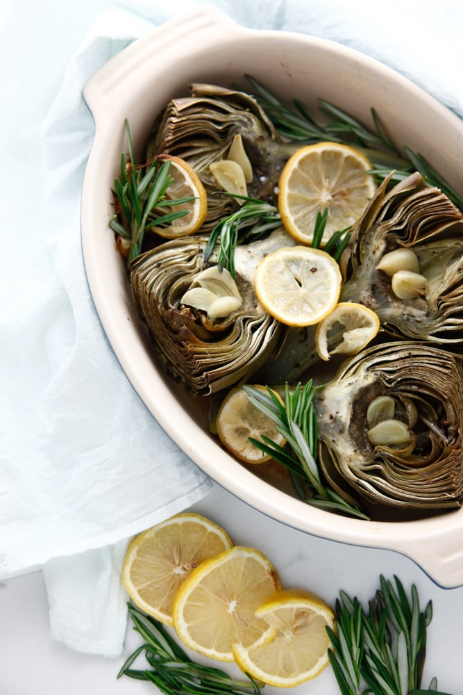 Lemon Rosemary Baked Artichokes in a baking dish from overhead.