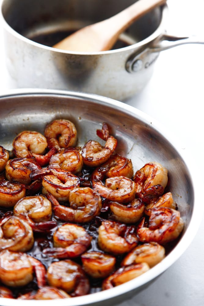 a skillet and saucepan of Honey BBQ Shrimp.