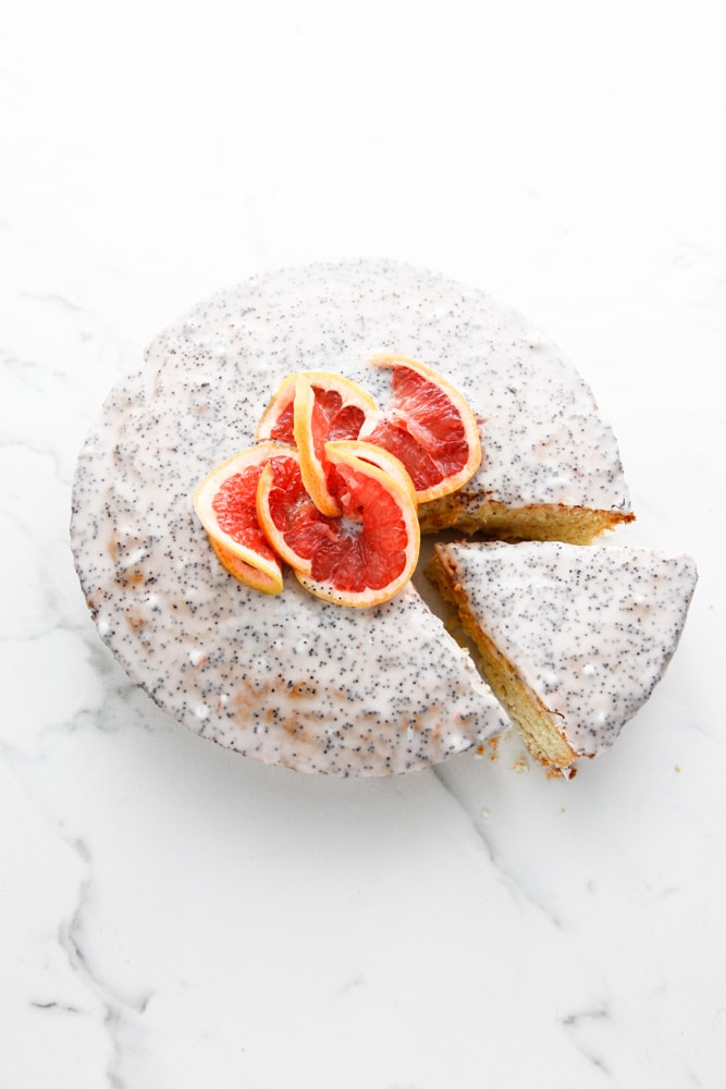 an overhead shot of Grapefruit Poppy Seed Cake with a slice being taken out.
