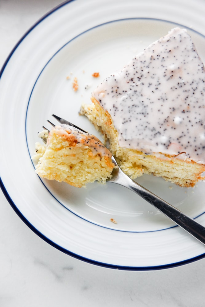 a slice of Grapefruit Poppy Seed Cake being cut with a black fork.