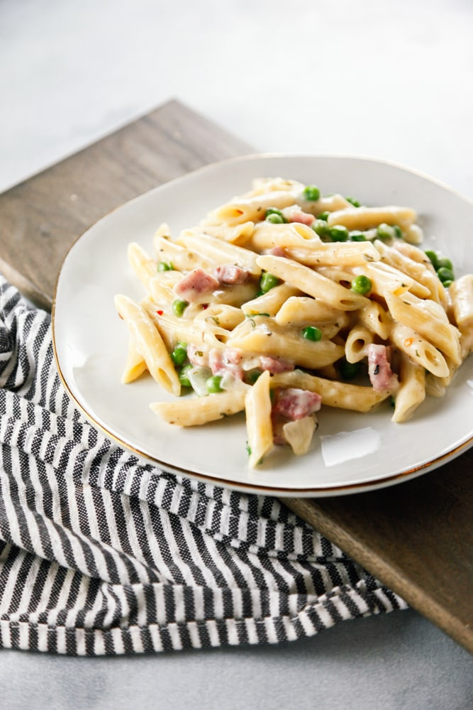 a white plate full of Ham and Peas Penne Pasta.