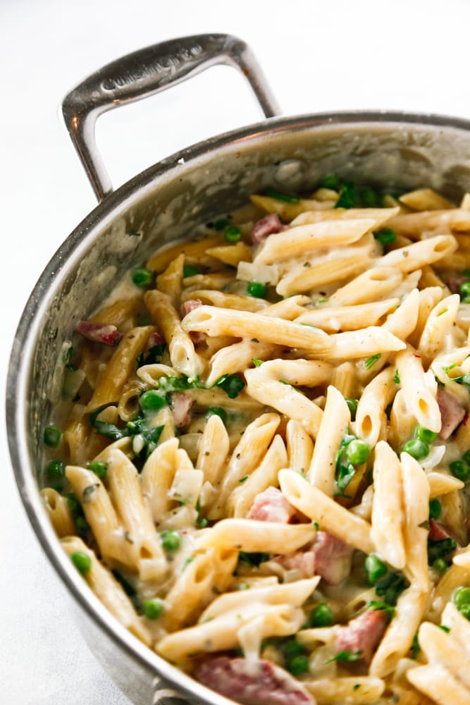 a saute pan full of Ham and Peas Penne Pasta.