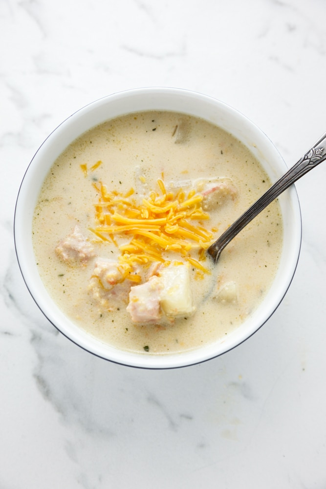 an overhead shot of Creamy Cheesy Ham and Potato Soup with a spoon and topped with cheese.