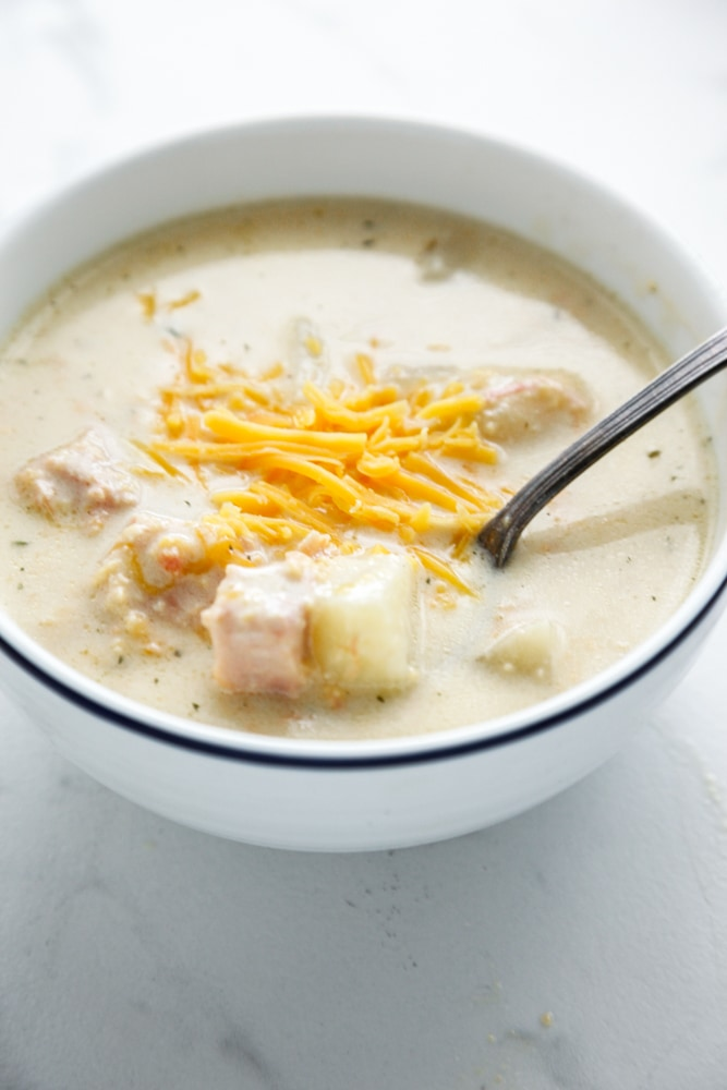 Creamy Cheesy Ham and Potato Soup in a white bowl with a blue stripe.