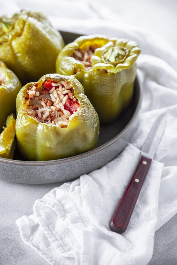 A grey tray of Baked Stuffed Bell Peppers with a paring knife by the side.