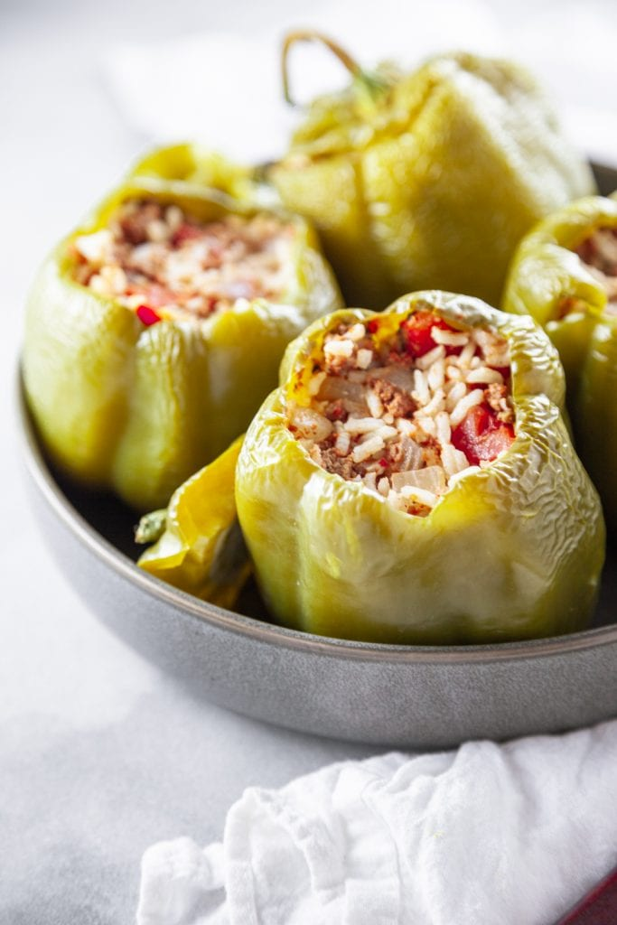 Baked Stuffed Bell Peppers in a grey bowl with the tops off.