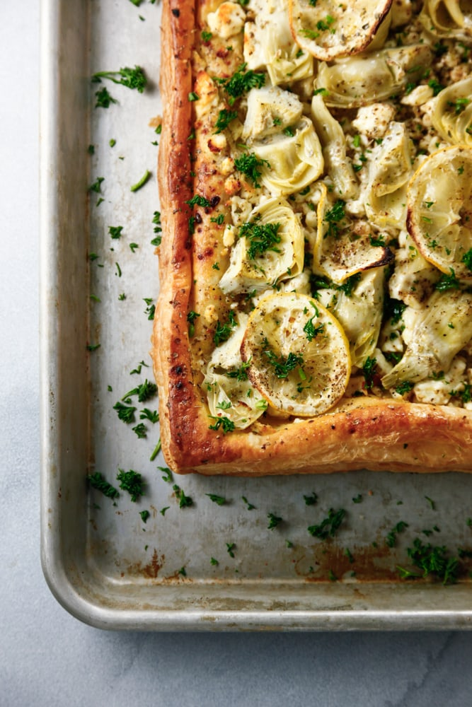 the edge of Mediterranean Puff Pastry Tart on a sheet pan.