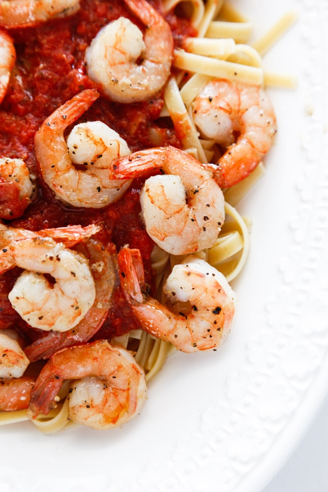 a plate of Spicy Shrimp Fra Diavolo over pasta.