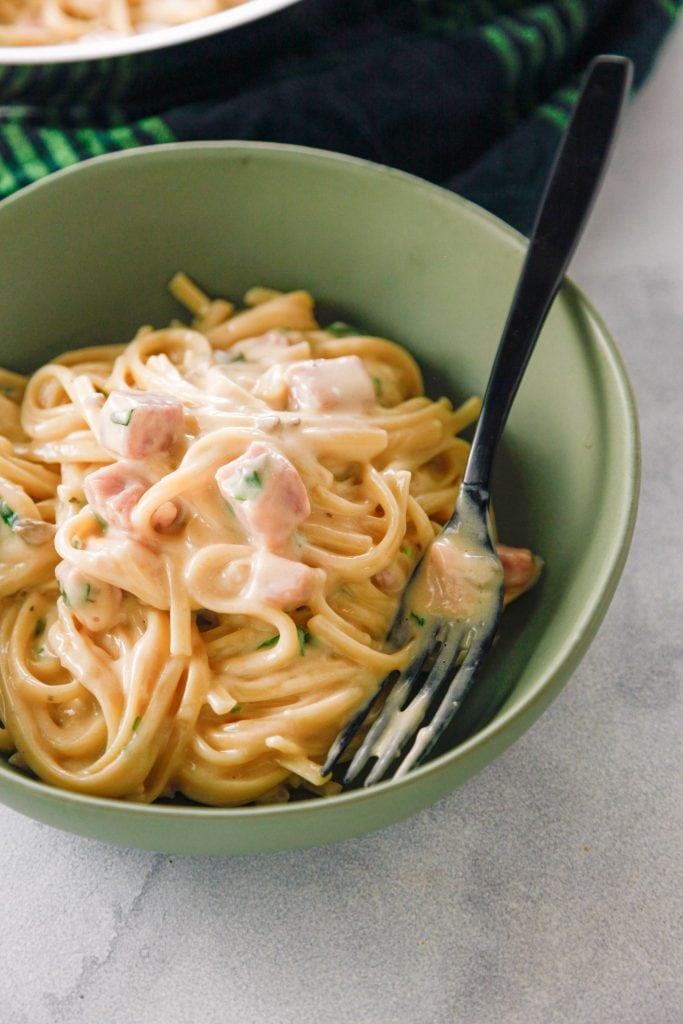 Easy Creamy Ham Tetrazzini in a green bowl with a black fork.