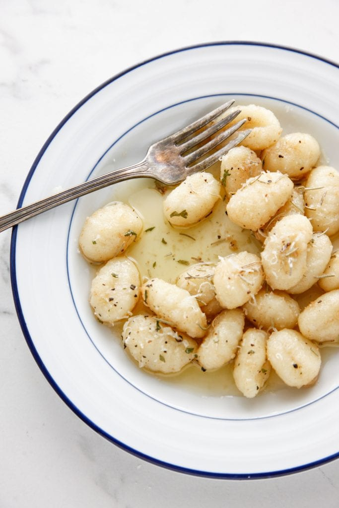 Brown Butter Gnocchi on a white and blue plate.