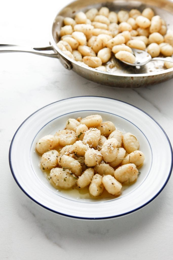 Brown Butter Gnocchi on a white and blue plate with a silver pan in the background.