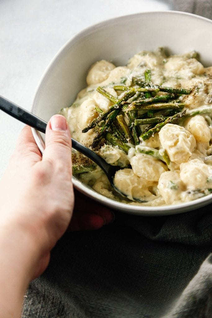 Creamy Asparagus Gnocchi in a white bowl held by a hand.