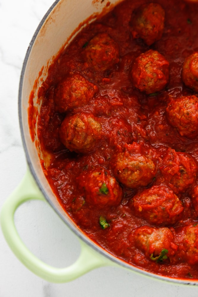 Easy Spicy Italian Meatballs in a green dutch oven.